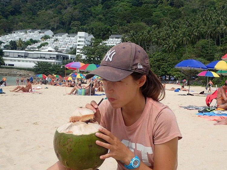 Emilie déguste sa noix de coco sur la plage