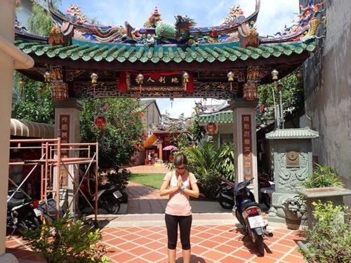 Emilie fait un waï devant l'entrée d'un temple
