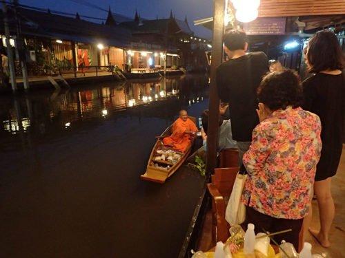 Un moine se déplace à bateau pour récupérer ses offrandes