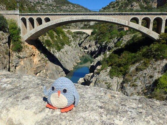 Pablo, le pingouin voyageur, sur le Pont du Diable
